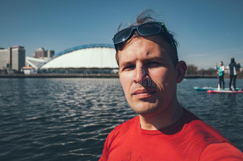 Open air Selfie of a young boy in Sunny day on background of the city. A man in a red t-shirt having fun together on a paddleboard. Open air Selfie of a young royalty free stock images