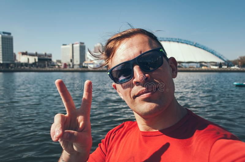 Open air Selfie of a young boy in Sunny day on background of the city. A man in a red t-shirt having fun together on a paddleboard royalty free stock images