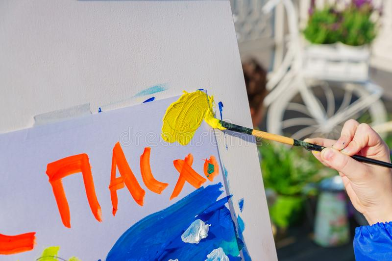 Open air workshop.  Easter Holiday festival in Moscow. A child paintis a picture for Easter. Easter inscription in Russian stock image