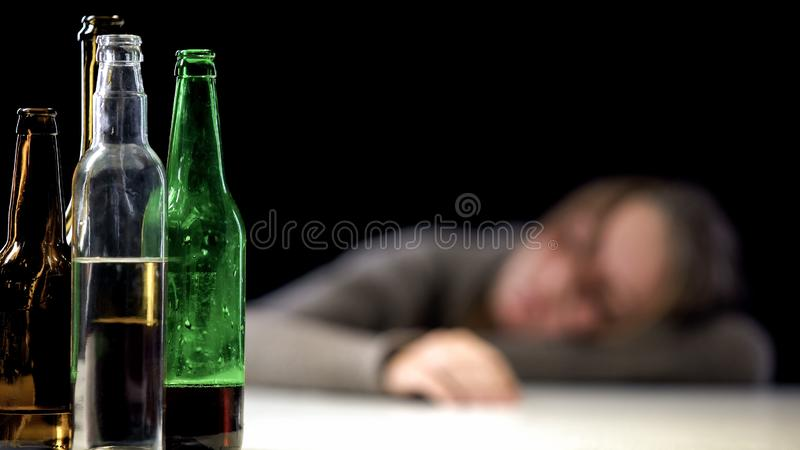 Open alcohol bottle on table with drunk sleeping woman on background, despair. Stock photo stock images