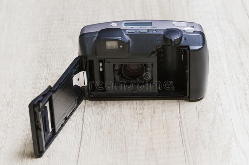 Analog camera open on a wooden board. Open analog camera without film roll on a wooden board royalty free stock photo