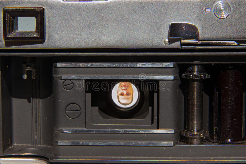 Open analog camera. With male portrait in lens stock photo