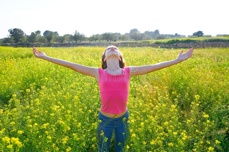 Open arms happy teen girl in spring meadow. Brunette stock photography