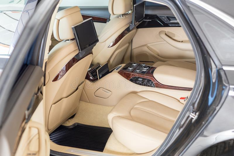 Open back door of business class car. Rear seat of modern luxury vehicle. Interior of limousine with entertainment stock photo
