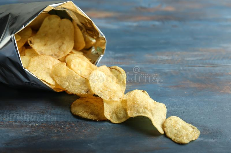 Open bag with crispy potato chips on color wooden table stock photography