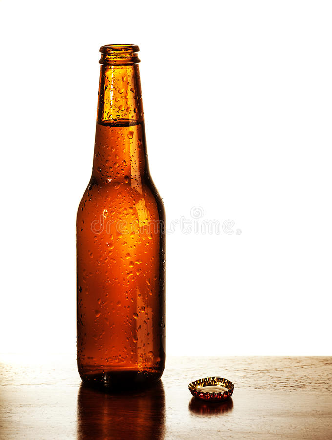Open beer bottle. Photo of open beer glass bottle with lid on the table on white background, alcohol beverage, cold bubbles drink, amber ale, brew pub, german stock images