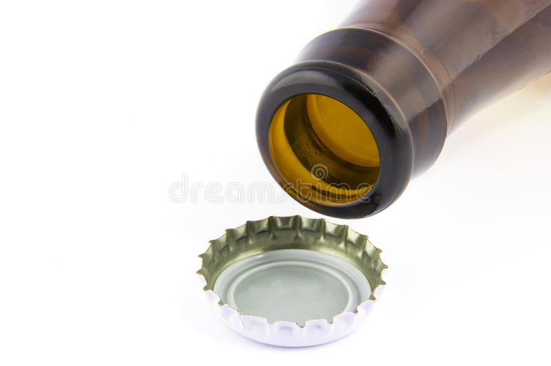 Open beer bottle and a cap stock photography