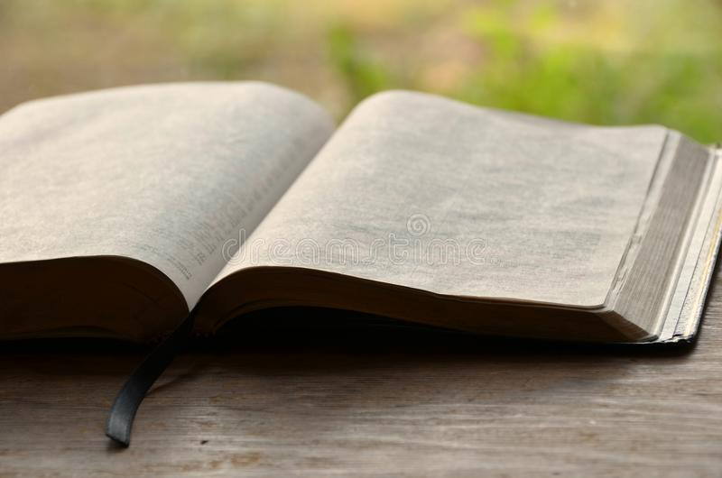Open Bible. On a wooden desk with blurred background stock images