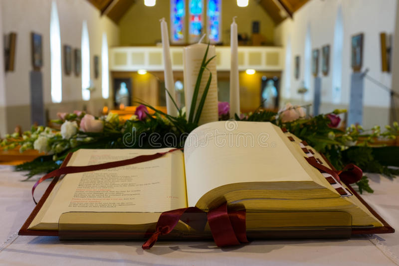 Open Bible in Church. Close up. Open Bible and wedding flowers on the altar in catholic church. Shallow DOF royalty free stock image