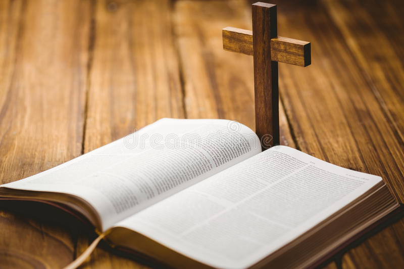 Open bible with crucifix icon behind. On wooden table stock images