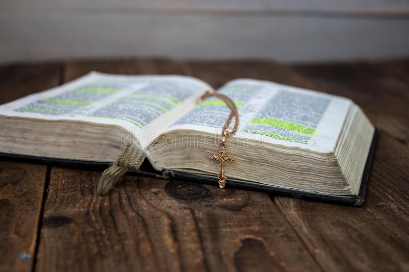 A open bible and golden cross on wooden background stock photos