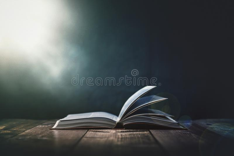 Open Bible with a light coming from above on a wooden desk royalty free stock image