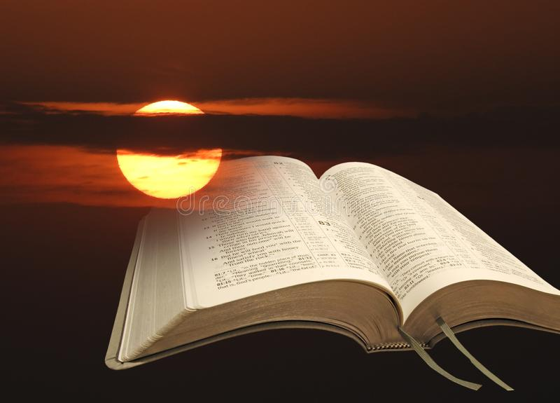 Open bible psalms holy word of god sunset sun heavens gospel. Concept photo of open holy bible psalms book set against a setting sun clouds background royalty free stock photo