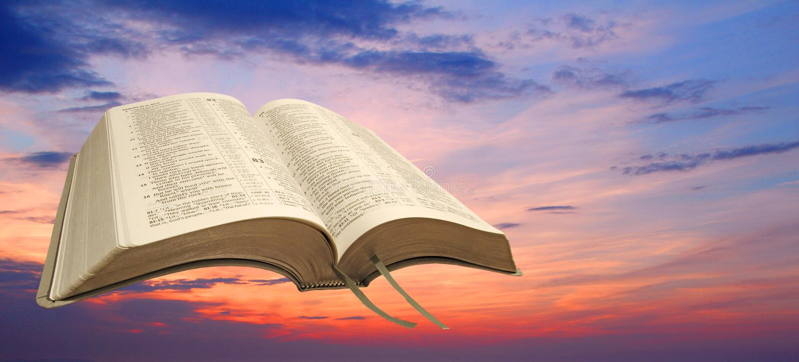 Open bible sunset sky. Photo of bible open at book of psalms with peaceful sunset sky ideal for own text etc stock photo