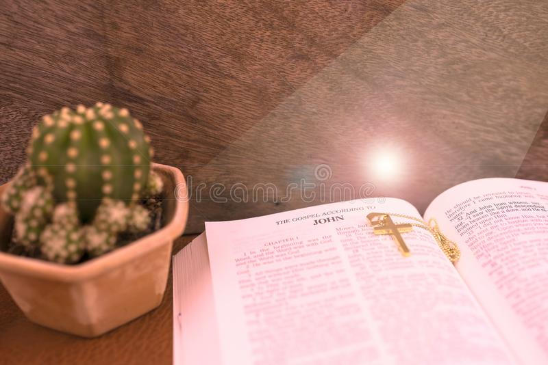 Open bible to open at The gospel According to JOHN and jesus on cross for concept inspiration. And empowering royalty free stock image