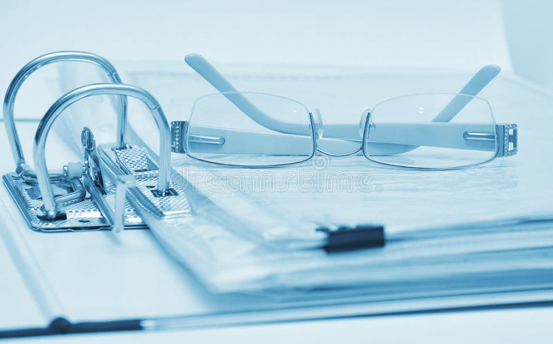 Open binder and glasses over document royalty free stock photos