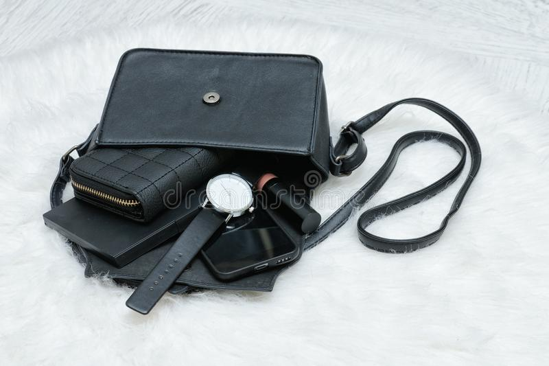 Open black bag with dropped things, notebook, mobile phone, watch and purse. Fur on background. Fashion concept.  stock photo