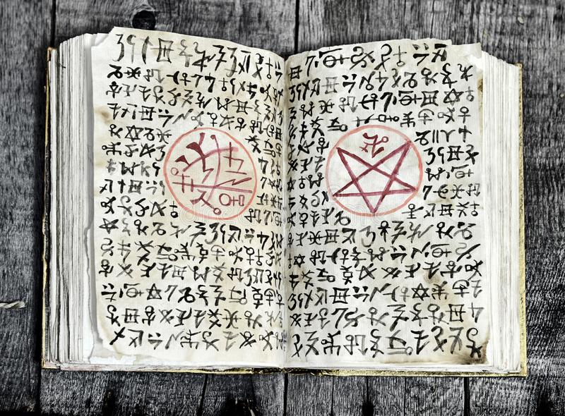Open black magic book with evil symbols and pentagram on shabby pages. Halloween, occult, esoteric and wicca concept. Vintage background with old magic objects royalty free stock photo
