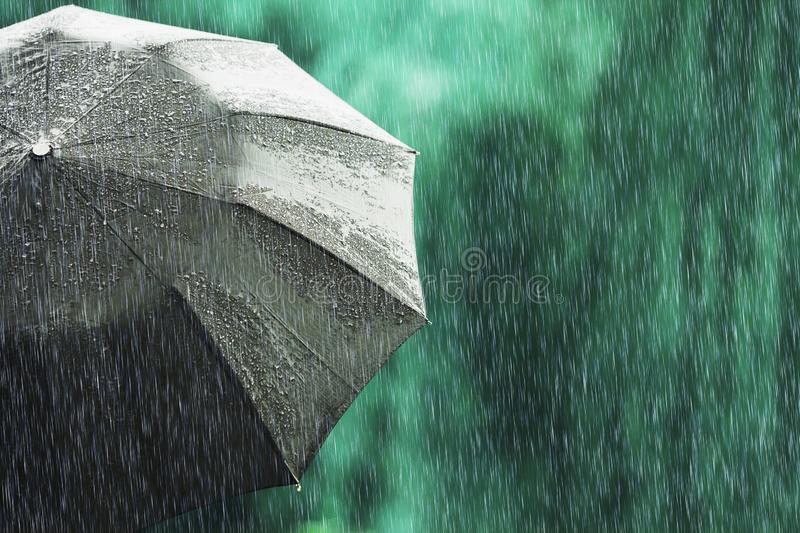 Open black umbrella in wet weather. Autumn rain. Deep sorrow. Wet umbrella against backdrop of street. Sad mood. Raining in city. royalty free stock image