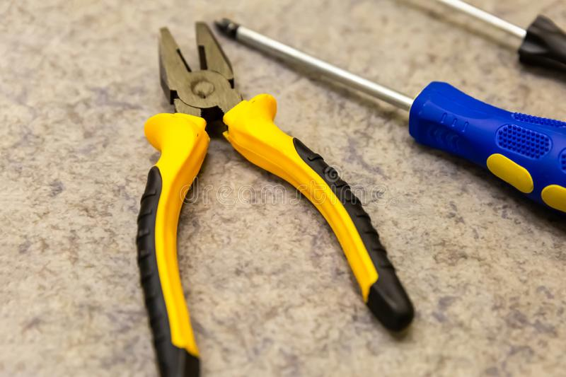 Open black and yellow pliers blue screwdriver closeup background building design web site royalty free stock image