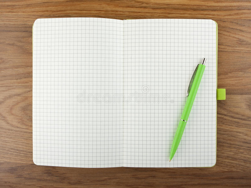 Open blank checked notebook with green pen on a table. royalty free stock photo