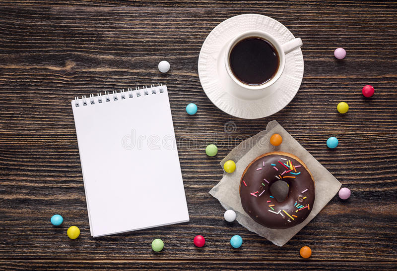 Open blank notebook, cup of coffee and a chocolate donut on a wooden table. Space for text. Top view royalty free stock photos