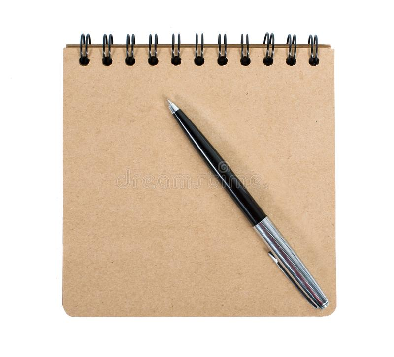Open blank square notebook of brown kraft paper with a spiral and ballpoint pen lie on a white background stock photo