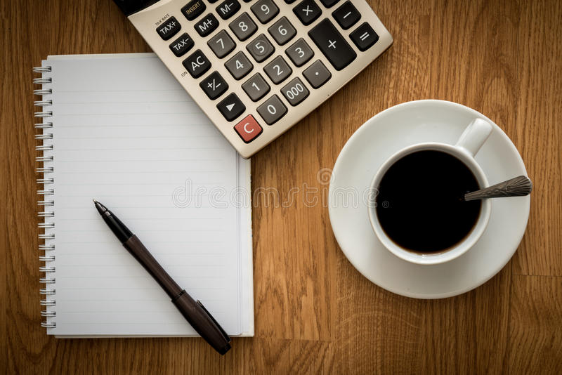 Open a blank white notebook, pen and cup of coffee and Calculator. On the desk royalty free stock image