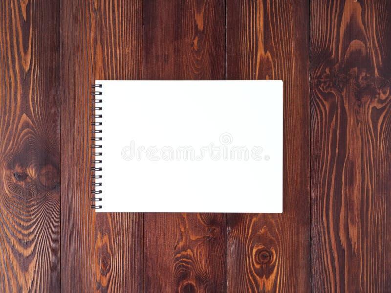 open blocnote met spiraal op donkere bruine houten lijst, hoogste mening stock fotografie