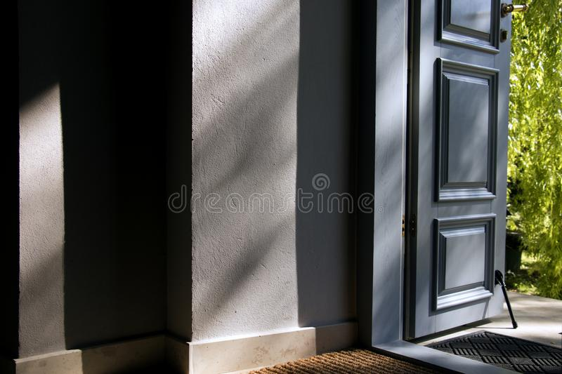 Open blue door into the house. Lights and shadows royalty free stock photo