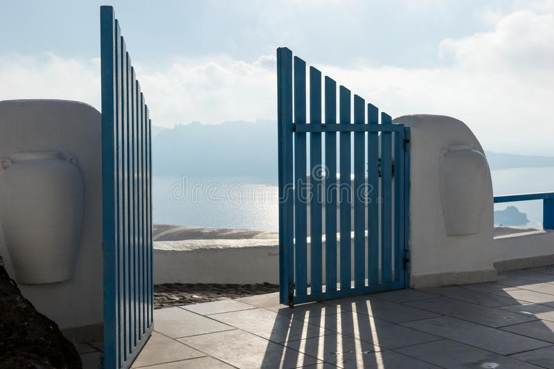 Open blue door overlooking the Mediterranean sea. In Santorini stock image