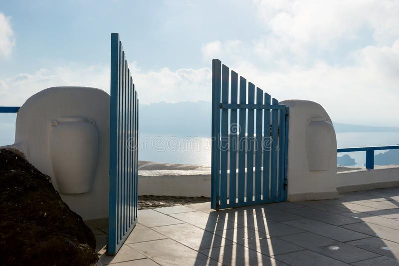 Open blue door overlooking the Mediterranean sea. In Santorini royalty free stock images