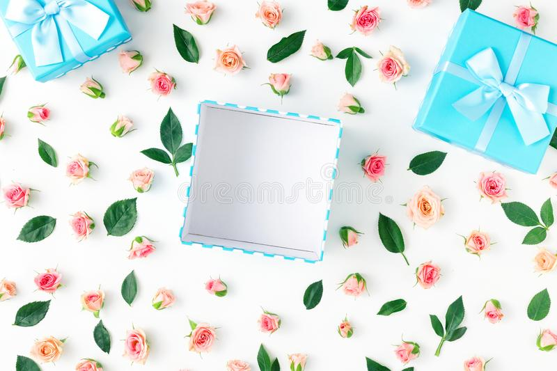 Open blue gift box with pink roses on white background. Open blue gift box with pink roses on a white background in flat lay style. Top view stock illustration