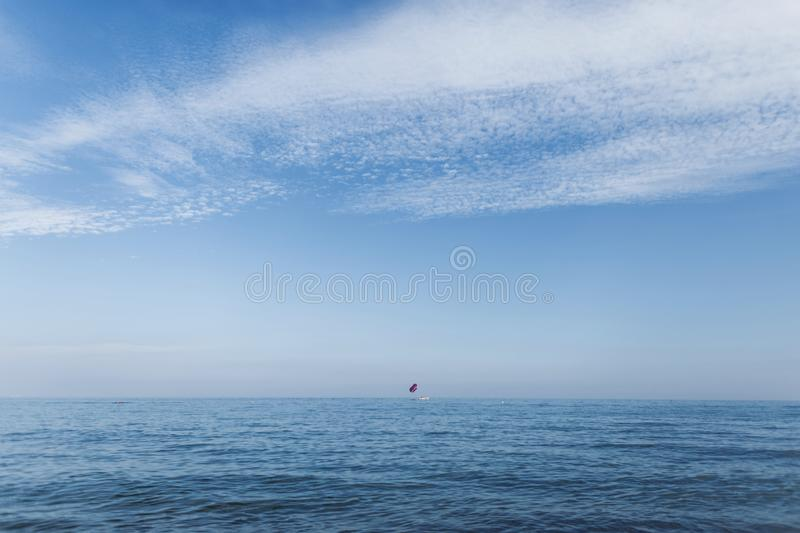 An open blue ocean with a blue sky with beautiful white clouds and a yacht far on the horizon. Traveling in Spain. Paradise. An open blue ocean with a blue sky royalty free stock photo