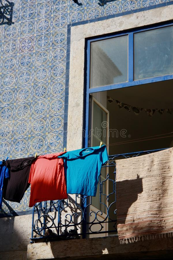 Open blue window on blue colored facade traditional portugal house. Open blue window on blue colored azulejo facade of traditional portugal house. Clothes stock photography