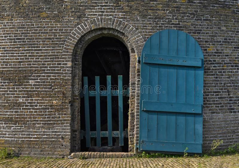 Open blue door on brick structure. Open blue wooden door on brick buidling royalty free stock images
