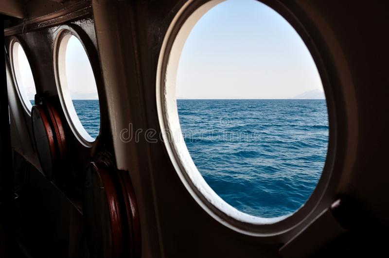 Open boat porthole with ocean view stock images