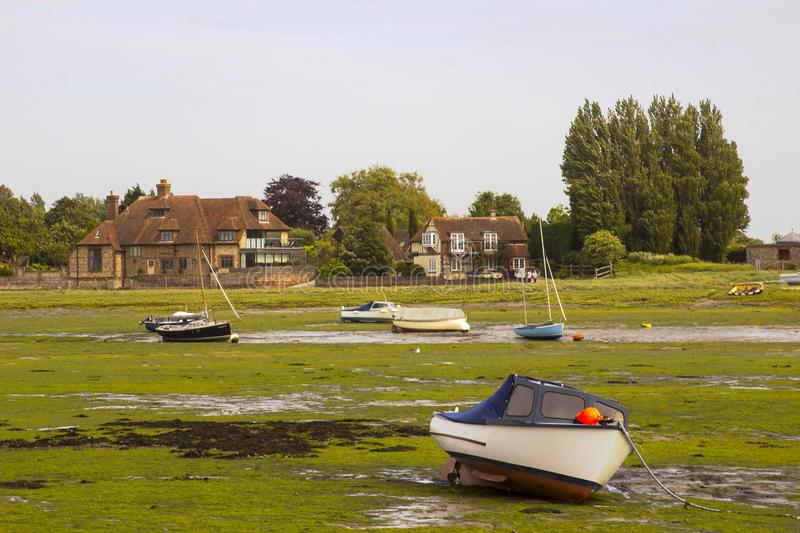 Open boats grounded at low tide in the historic harbour at Bosham in West Sussex in the South of England royalty free stock photography