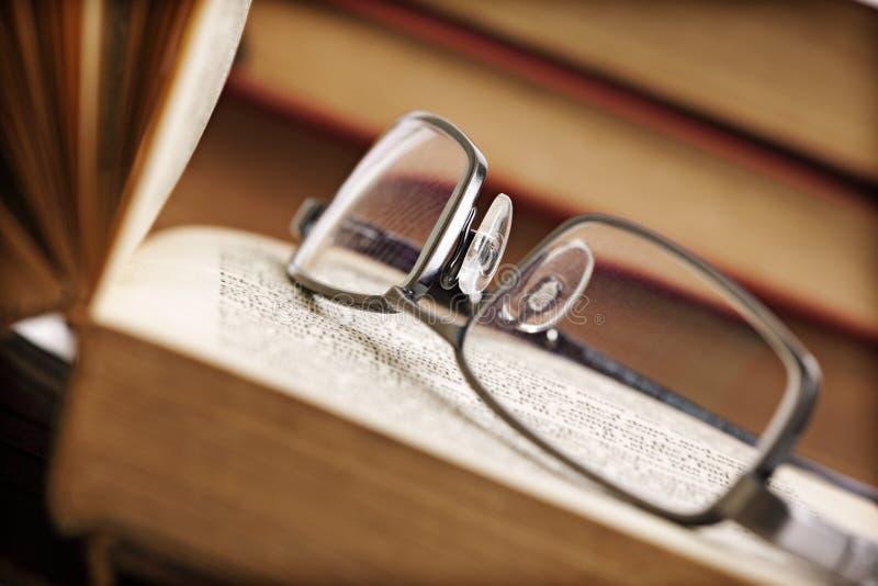 Open boek en bril stock afbeeldingen