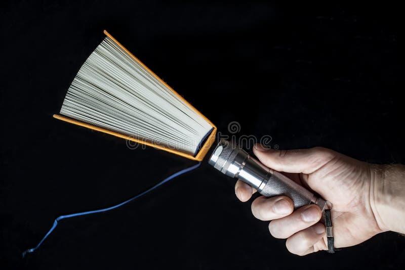 Open boek en een flitslicht in de hand van de mens royalty-vrije stock afbeelding