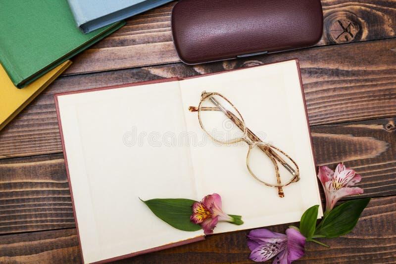 Open boek met bloemen en glazen op een houten achtergrond stock afbeeldingen