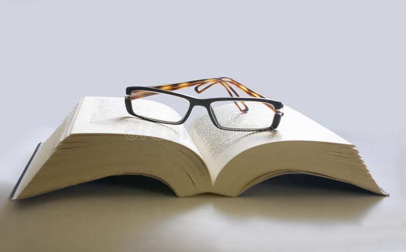 Open boek met glazen stock afbeelding
