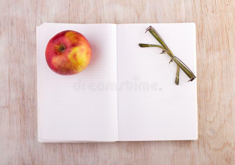 Open boek met glazen en appel op bureau royalty-vrije stock afbeeldingen
