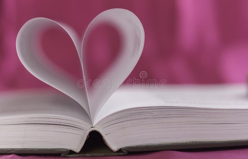 Open boek met hartvorm stock afbeelding