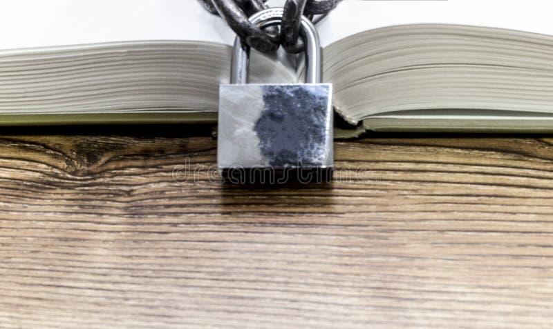 Open boek met ketting en slot op houten lijst royalty-vrije stock afbeeldingen