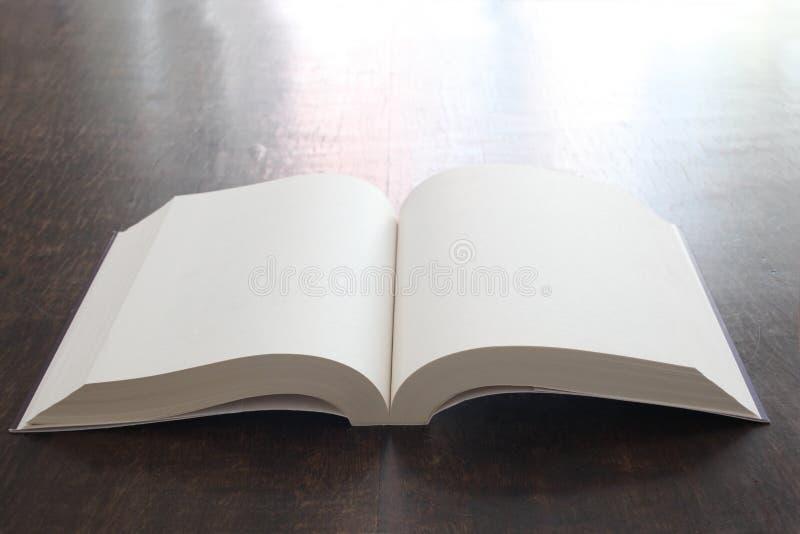 Open boek met lege pagina's op een houten lijst met exemplaarruimte stock afbeeldingen