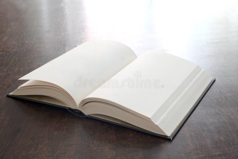 Open boek met lege pagina's op een houten lijst met exemplaarruimte stock afbeelding