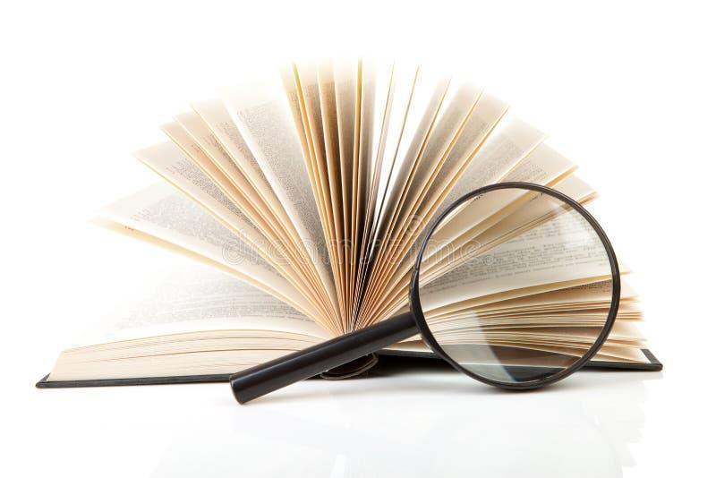 Open boek met vergrootglas royalty-vrije stock afbeeldingen