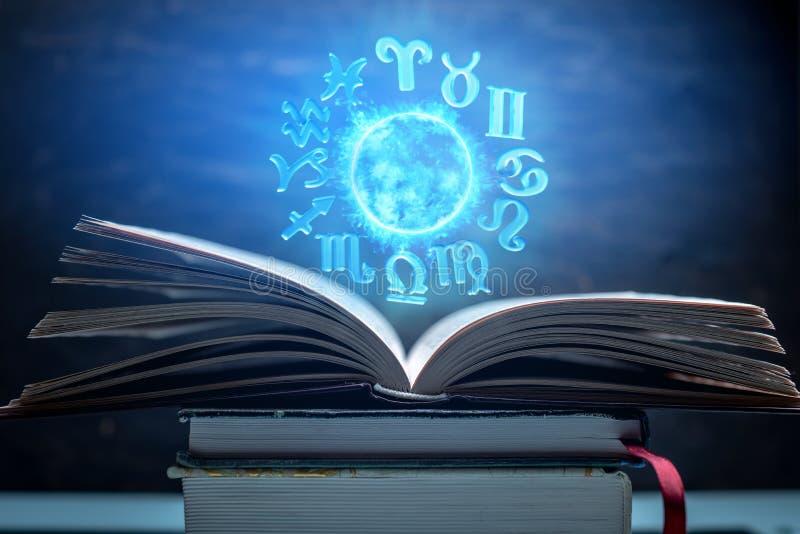 Open boek op astrologie op een donkere achtergrond De gloeiende magische bol met tekens van de dierenriem in het blauwe licht royalty-vrije stock fotografie