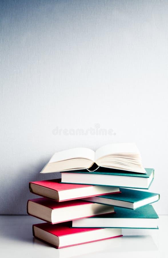 Open boek op een groene en rode stapel van boeken stock fotografie